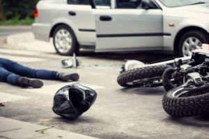 motorcycle rider on the ground with helmet off and motorcycle on the side after an accident